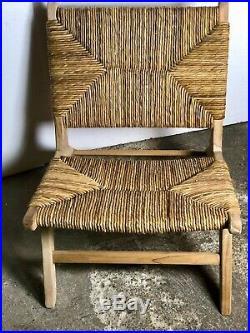 Fauteuil bas en teck brut avec assise et dossier paillé style Charlotte Perriand